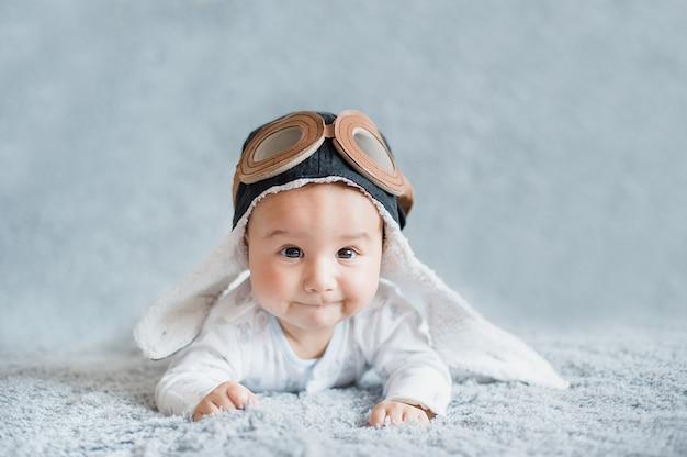 パイロットの帽子でかわいい微笑の赤ん坊。航空の日。