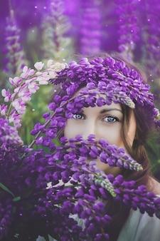 フィールドに日没でルピナスの花束を保持しているウルトラバイオレットと白のドレスで美しい若い女性。自然とロマンスの概念。調子
