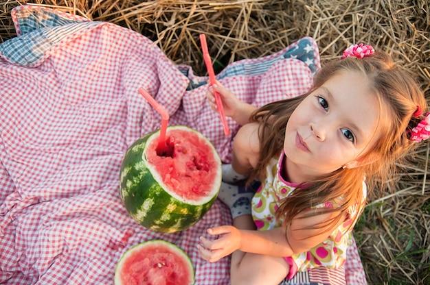 スイカを食べる少女。フィールドで幸せな子。夏の気分。