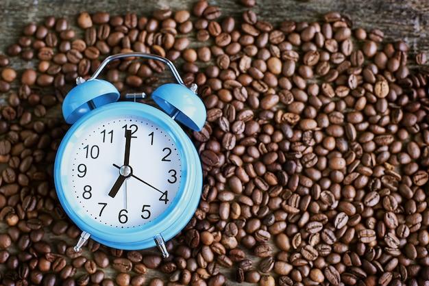 Жареный кофе в зернах с будильником. утренняя концепция