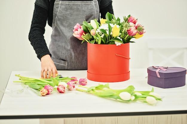 花と花屋のクローズアップ手。ピンクのチューリップの咲く花束を保持している花屋。フラワーショップのコンセプト。コピースペース