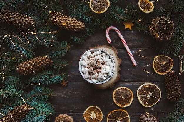 クリスマスキャンディケインの枝ホットチョコレート飲料は暗いテーブルにオレンジスライスを乾燥