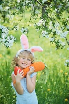 Милая смешная девушка с пасхальными яйцами и ушами зайчика на саде. пасхальная концепция. смеющийся ребенок на пасхальной охоте на яйца