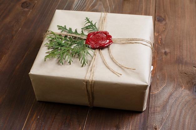 クラフト紙で包まれた贈り物、ひもと糊付けされたワックスシールで結ばれる。テーブルの上に横になっています。
