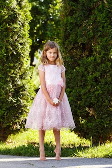 公園の緑豊かなピンクのドレスで陽気な女の子の肖像画。