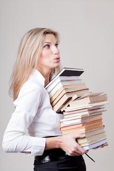 書籍のスタックを保持している女の子