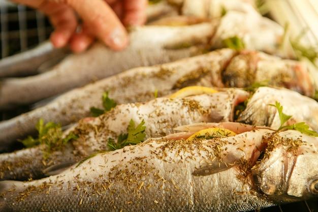 男は魚のスパイスと調味料を振りかけます