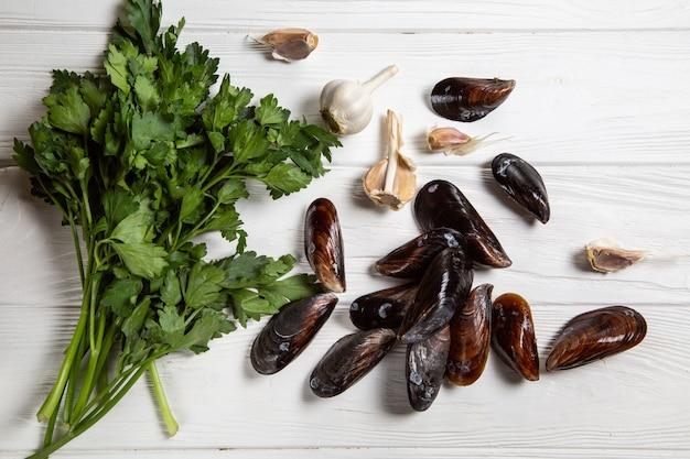 Приготовить ингредиенты, свежие сырые мидии с петрушкой и чесноком