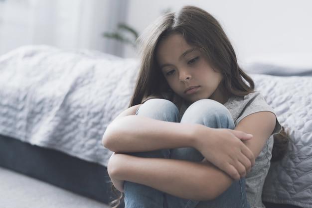 Грустная девушка обвивает ноги и сидит на полу в спальне