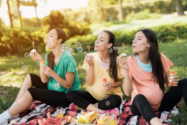 腹の女性は公園でシャボン玉を吹いています。