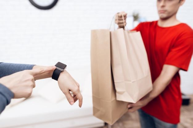 Курьер с пакетами и женщина с часами на руке.