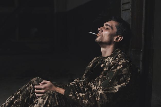 戦後の男は喫煙して落ち込んだ。