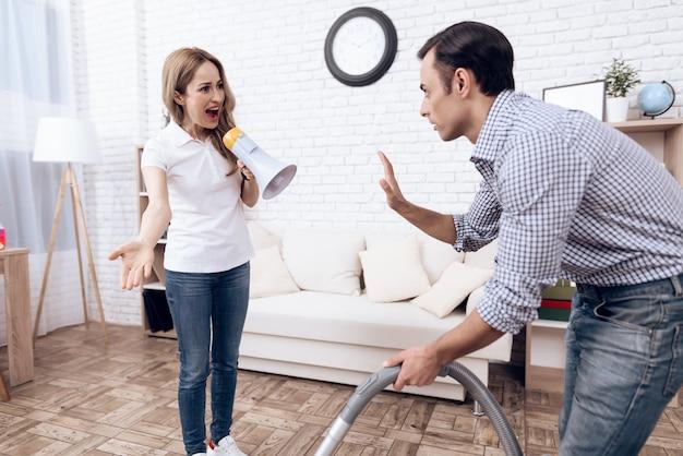 掃除機とアパートの女性を持つ男。