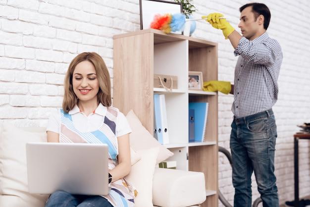 男はソファの棚と女性からほこりを取り除きます。