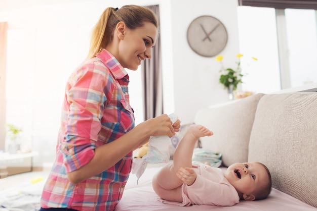Женщина пеленает маленького ребенка на диване.