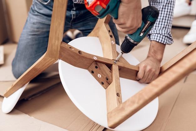Сборщик мебели с дрелью в руках ремонтирует кресло.
