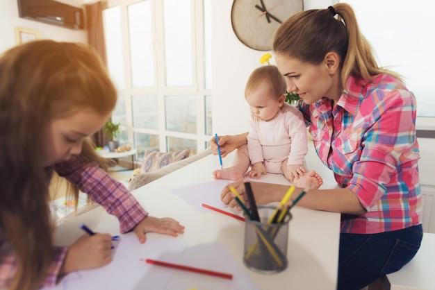 Маленькая девочка рисует на кухне сверху цветными карандашами.