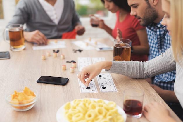 Компания молодых людей играет в русское лото.