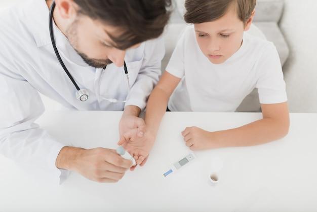 内分泌専門医が赤ちゃんの指から血液サンプルを採取します。