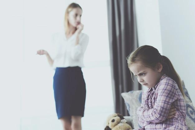 女性は電話で話しています。気分を害した少女はソファに座っています。
