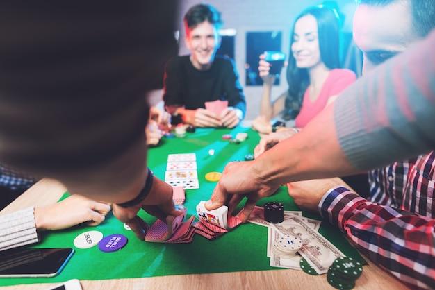 Человек тасует карты за игровым столом.