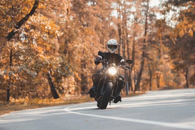 ヘルメットをかぶった若い男が林道に乗っています。