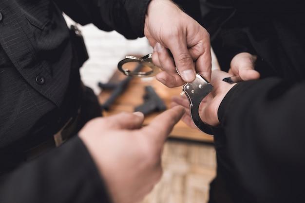 警察官は、手錠の使用方法を部下に示します。