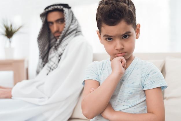 伝統的なアラブ家族の男の子は両親に腹を立てています。