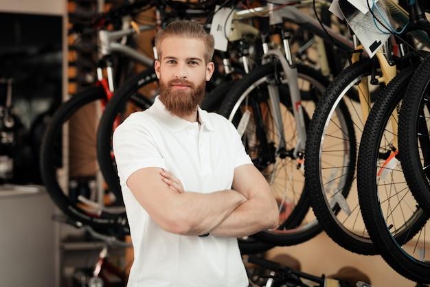 自転車屋のセールスマンが自転車の近くでポーズをとります。