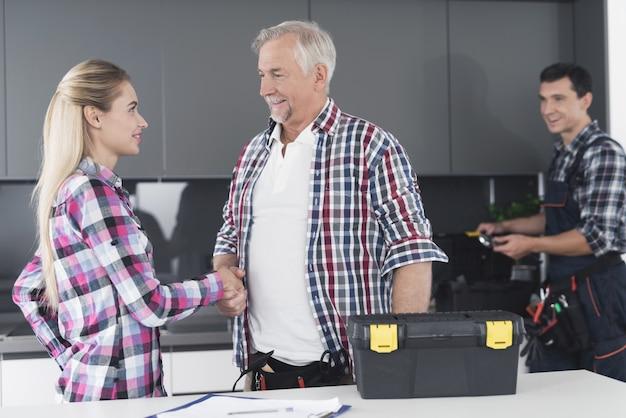 Женщина пожимает руку и благодарит сантехников за ремонт.