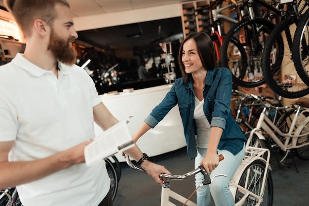 若い女の子が彼女の店でシティバイクを選択します。