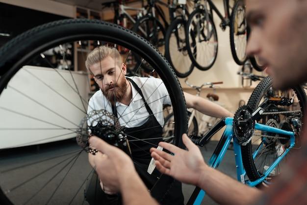 若い男が自転車を修理するためにワークショップに来ました。