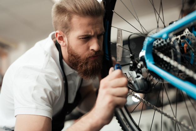 若い男が自転車を修理します。彼はエプロンを着ています。