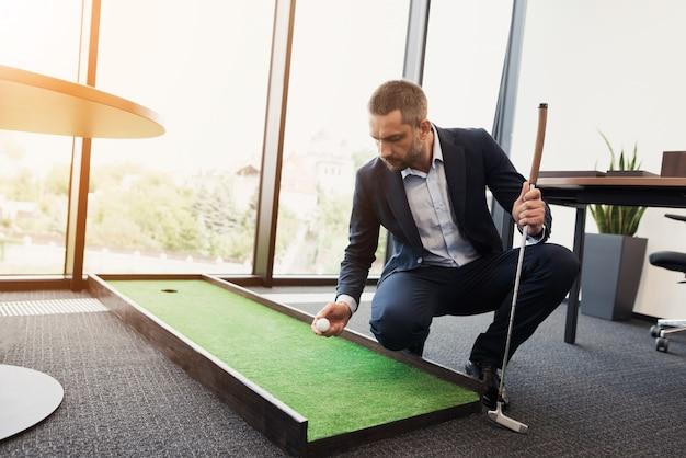 厳格なビジネススーツを着た男は、ミニゴルフのオフィスで遊ぶ。