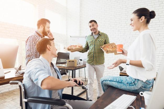 若い人たちはオフィスでピザとランチを持っています。