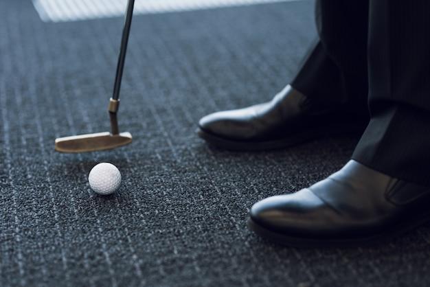 閉じる。灰色のカーペットの上にゴルフクラブとゴルフボール。