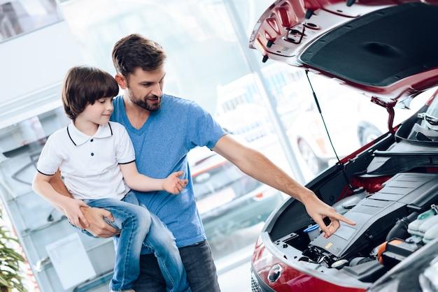 息子を腕に抱いたお父さんは、車の中でエンジンがどのように機能するかを示しています。
