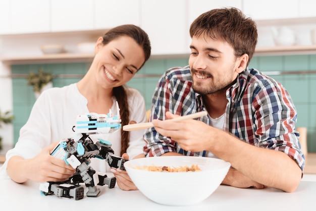 男と少女は小さなサイのロボットに餌をやっています。