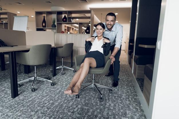 男が従業員をオフィスの椅子に転がします。