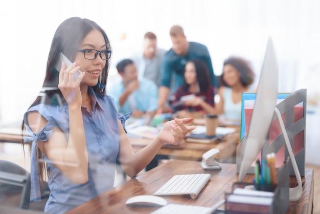 アジアの女の子はオフィスに電話で話しています。