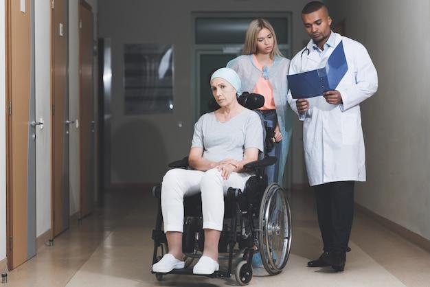 がんの女性は車椅子に座っています。