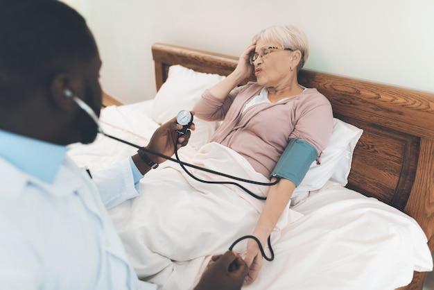 医師は老人ホームで高齢の患者を診察します。