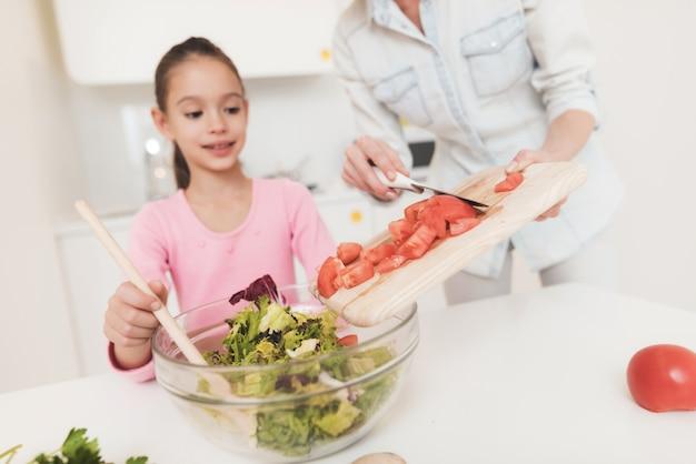 女の子は、明るいキッチンでサラダを準備することを学んでいます。