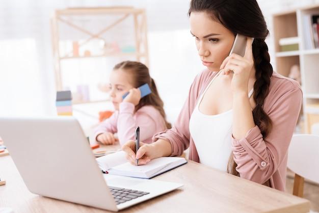 Маленькая девочка копирует маму с телефоном в руке дома.