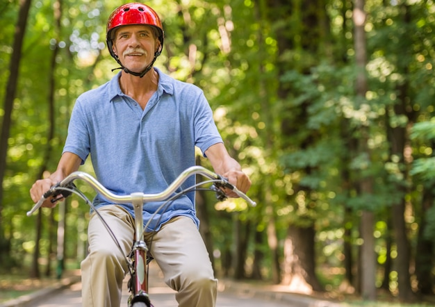 ヘルメットの年配の男性は公園で自転車に乗っています。