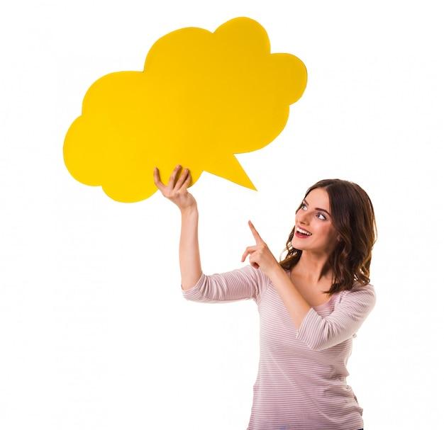 テキストの黄色のバブルを保持している幸せな若い女の子。