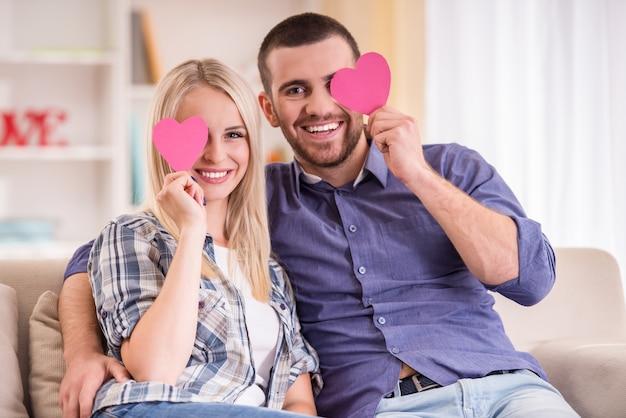 自宅のソファに座っているカップルは、カメラを見てください。