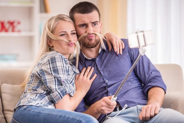 電話を使用して、自宅でソファに座っているカップル。