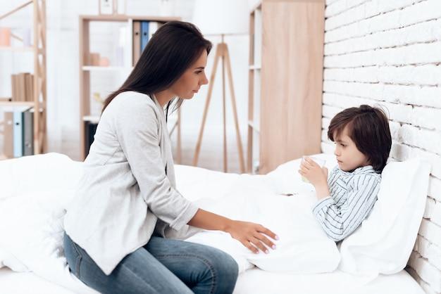 病気の息子横になっているベッドに薬を与える母