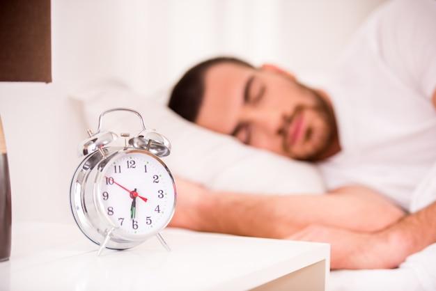 自宅の快適なベッドで寝ている若い男。